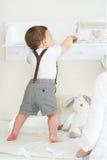 Gulligt behandla som ett barn pojken som hemma spelar och att tycka om himslef royaltyfri fotografi