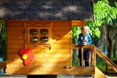 Gulligt behandla som ett barn pojken som leker i treehuset som är utomhus- Arkivbilder