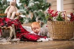 Gulligt behandla som ett barn pojken som ligger på golv bland julpynt Royaltyfri Foto
