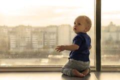 Gulligt behandla som ett barn pojken som ser till och med fönstret till den regniga storstaden Begynnande pojke som väntar på för Arkivfoton