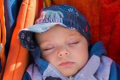Gulligt behandla som ett barn pojken som sover i en sittvagn Arkivbilder