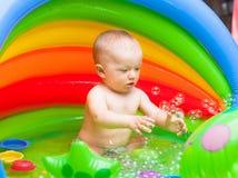 Gulligt behandla som ett barn pojken som spelar med bubblor i en ungepöl Arkivbilder