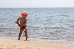 Gulligt behandla som ett barn pojken som spelar med strandleksaker Arkivfoton