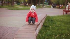 Gulligt behandla som ett barn pojken som spelar utomhus- squatting på parkera nära till det gröna gräset och att se omkring arkivfilmer