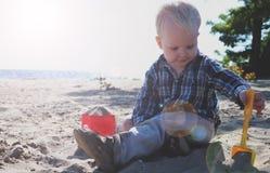 Gulligt behandla som ett barn pojken som spelar med strandleksaker på den tropiska stranden arkivfoton