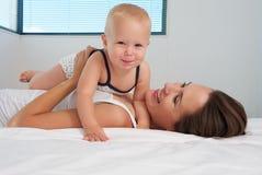 Gulligt behandla som ett barn samman med lycklig barnmoder Arkivbilder