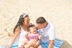Gulligt behandla som ett barn skratta för unga föräldrar litet barndottern med kyssfläcken på kindsammanträde på stranden som ler Fotografering för Bildbyråer
