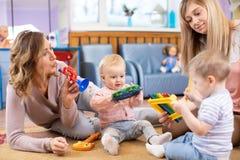 Gulligt behandla som ett barn spela musikal leker med läraren och assistenten Tidig musikalisk utbildning i dagis fotografering för bildbyråer