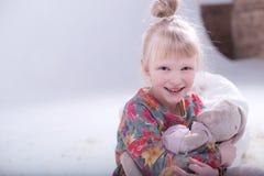Gulligt blont barn i en vit studio fotografering för bildbyråer