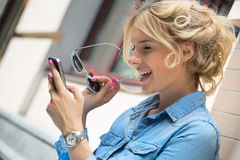 Gulligt blont samtal på en mobiltelefon Royaltyfria Bilder