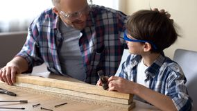 Gulligt bulta för pys spikar i träplankan, fadern som lovordar hans unge, service royaltyfri fotografi