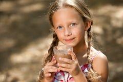 Gulligt dricka för flicka mjölkar choklad. Arkivfoton