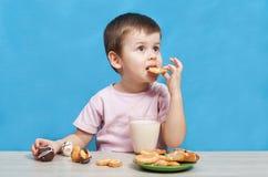 Gulligt dricka för pys mjölkar och att äta kakor arkivbild