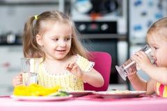 Gulligt dricksvatten för små barn på daycare Arkivbild