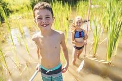 Gulligt flicka- och pojkefiske med ett netto på en sjö royaltyfria bilder