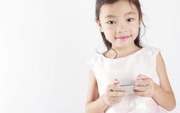 Gulligt flickabruk en mobiltelefon Royaltyfri Bild