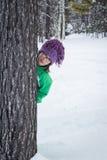 Gulligt flickanederlag bak ett träd i snöig skog Arkivbild