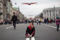 Gulligt flickasammanträde på vägen i mitt av gatan royaltyfri foto