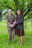 Gulligt gammalt gift par som poserar för en stående i deras trädgård Förälskelseför evigtbegrepp Arkivfoton