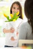 Gulligt ge sig för flicka blommar hennes mamma Fotografering för Bildbyråer