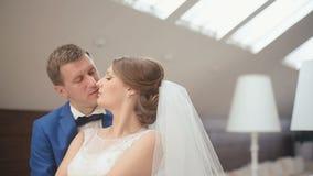 Gulligt gift par i det lyxiga kafét Mjukt ögonblick för närbild av bruden och slappt att le för brudgum den kyssande stock video