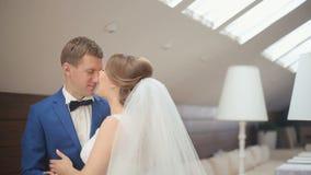 Gulligt gift par i det lyxiga kafét Roligt ögonblick för närbild av brudgummen och bruden som ler och flörtar slappt med lager videofilmer