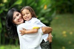 Gulligt gladlynt barn med modern Royaltyfri Bild