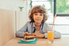 gulligt gladlynt lockigt pojkesammanträde i kafé i kafé med stycket av kakan arkivfoto