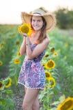 Gulligt härligt sammanträde för ung flickadamkvinna på ett fält med stora solrosor Brunett med att bära för blåa ögon som är färg royaltyfria foton