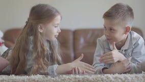 Gulligt kopplar samman lite pojke- och flickalögn på mattan och att tala om något roligt spela, att skratta och att le stock video