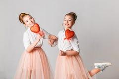 Gulligt kopplar samman systrar med röda hjärtor på pinnar Fira Sankt dag för valentin` s royaltyfri bild