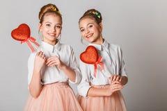 Gulligt kopplar samman systrar med röda hjärtor på pinnar Fira Sankt dag för valentin` s royaltyfri fotografi