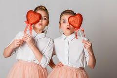 Gulligt kopplar samman systrar med röda hjärtor på pinnar Fira Sankt dag för valentin` s arkivfoto