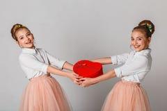 Gulligt kopplar samman systrar som packar upp den röd hjärta formade gåvan Fira Sankt dag för valentin` s fotografering för bildbyråer