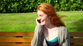 Gulligt kvinnasammanträde på bänk, medan ringa lager videofilmer