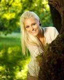 Gulligt kvinnlignederlag bak en tree Royaltyfri Bild