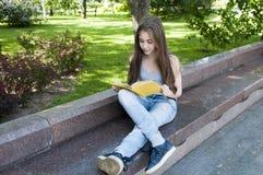 Gulligt läseboksammanträde för den tonårs- flickan på bänken parkerar in, att studera som är utomhus- Arkivbild
