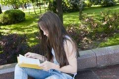 Gulligt läseboksammanträde för den tonårs- flickan på bänken parkerar in, att studera som är utomhus- Royaltyfri Fotografi