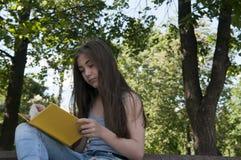 Gulligt läseboksammanträde för den tonårs- flickan på bänken parkerar in, att studera som är utomhus- Royaltyfria Foton
