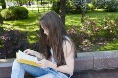 Gulligt läseboksammanträde för den tonårs- flickan på bänken parkerar in, att studera som är utomhus- Arkivfoto