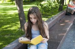 Gulligt läseboksammanträde för den tonårs- flickan på bänken parkerar in, att studera som är utomhus- Arkivfoton