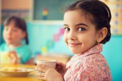 Gulligt latinamerikanskt dricka för flicka mjölkar på skolan Royaltyfri Bild