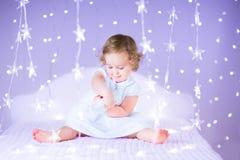 Gulligt le behandla som ett barn flickan på säng mellan härliga purpurfärgade ljus Royaltyfria Bilder