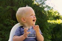 Gulligt le behandla som ett barn pojken med ett exponeringsglas av vattensammanträde i en behandla som ett barnstol mot den gröna Arkivfoton