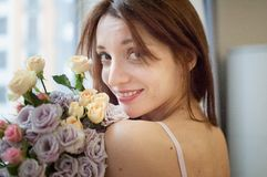 Gulligt le vuxet flickaanseende nära fönstret med en bukett av blommor och att se kameran Väntande på a royaltyfri foto