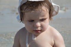 Gulligt ledset behandla som ett barn med sunscreenkräm på kind mot havsbakgrund Nätt begynnande flicka i den vita hatten och med  fotografering för bildbyråer