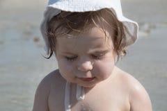 Gulligt ledset behandla som ett barn med sunscreenkräm på kind mot havsbakgrund Nätt begynnande flicka i den vita hatten och med  arkivbilder
