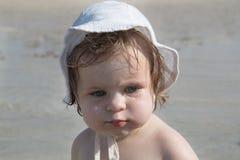 Gulligt ledset behandla som ett barn med sunscreenkräm på kind mot havsbakgrund Nätt begynnande flicka i den vita hatten och med  royaltyfri bild