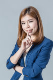 Gulligt leende för härlig asiatisk businesswomanwith som isoleras på gråa lodisar fotografering för bildbyråer