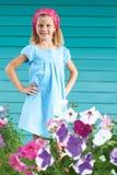 gulligt liten flickaanseende i trädgården som omges av blommor Arkivfoton